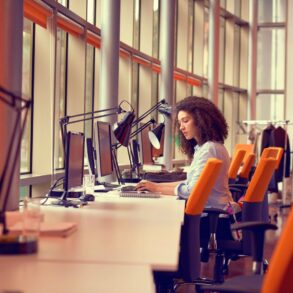 Young woman working on a computer at a job - row of desks